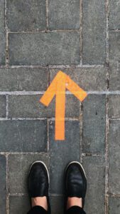 An orange arrow pointing in the direction of a person's next step